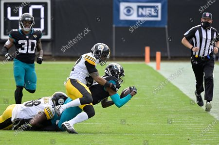 Jacksonville Jaguars wide receiver DJ Chark Jr. is tackled by Pittsburgh Steelers linebacker Vince Williams (98) and cornerback Steven Nelson (22) after catching a pass during the first half of an NFL football game, in Jacksonville, Fla