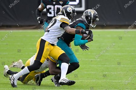 Jacksonville Jaguars wide receiver DJ Chark Jr., right, is tackled by Pittsburgh Steelers linebacker Vince Williams (98), below, and cornerback Steven Nelson (22) after catching a pass during the first half of an NFL football game, in Jacksonville, Fla