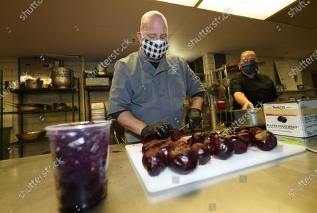 Stephen Tanner, owner of Elevated Catering, front, cuts beets for a salad as Lea Cookson, executive chef, works to prepare Thanksgiving Day dinner for clients in a kitchen in a school, in southwest Denver. In response to COVID-19, Tanner has changed the face of his business from cooking for large events to smaller gatherings and individual orders to keep his business afloat in these turbulent times
