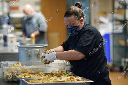 Stock Photo of As Stephen Tanner, owner of Elevated Catering, toils in the back, Lea Cookson, executive chef, works to prepare Thanksgiving Day dinner for clients in a kitchen in a school, in southwest Denver. In response to COVID-19, Tanner has changed the face of his business from cooking for large events to smaller gatherings and individual orders to keep his business afloat in these turbulent times