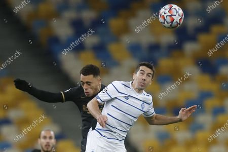 Barcelona's Sergino Dest, left, jumps for the ball with Dynamo Kyiv's Carlos de Pena during the Champions League group G soccer match between Dynamo Kyiv and FC Barcelona at the Olimpiyskiy Stadium in Kyiv, Ukraine