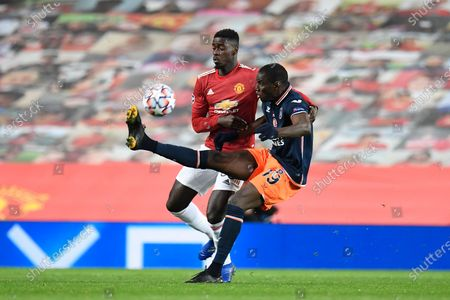 Axel Tuanzebe of Manchester United (L) and Demba Ba of Istanbul Basaksehir (R) in action during the UEFA Champions League group H soccer match between Manchester United and Istanbul Basaksehir in Manchester, Britain, 24 November 2020.