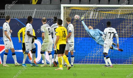Brugge's goalkeeper Simon Mignolet unsuccessfully dives to save a goal by Dortmund's Jadon Sancho, unseen, during the Champions League group F soccer match between Borussia Dortmund and Club Brugge in Dortmund, Germany