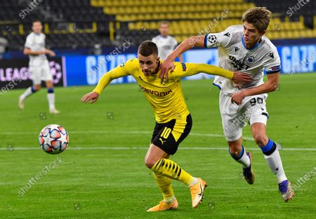 Brugge's Charles De Ketelaere, right, tries to stop Dortmund's Thorgan Hazard, left, during the Champions League group F soccer match between Borussia Dortmund and Club Brugge in Dortmund, Germany
