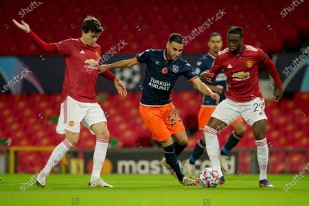 Basaksehir's Aziz Behich fights for the ball against Manchester United's Aaron Wan-Bissaka and Victor Lindelof, left, during the Champions League Group H soccer match between Manchester United and Istanbul Basaksehir at Old Trafford in Manchester, England