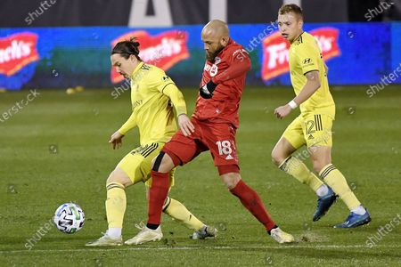 Toronto FC's Nick DeLeon, center, challenges Nashville SC's Alex Muyl, left, as Nashville's Alistair Johnston watches during the first half of an MLS soccer playoff match, in East Hartford, Conn