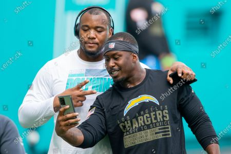 From left, Miami Dolphins defensive tackle Raekwon Davis and Los Angeles Chargers nose tackle Damion Square smile as they take a selfie on the field before an NFL football game, in Miami Gardens, Fla