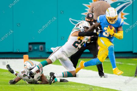 Los Angeles Chargers running back Kalen Ballage (31) runs with the ball and is pushed out of bounds by Miami Dolphins safety Brandon Jones (29) along with Miami Dolphins cornerback Byron Jones (24) during an NFL football game, in Miami Gardens, Fla