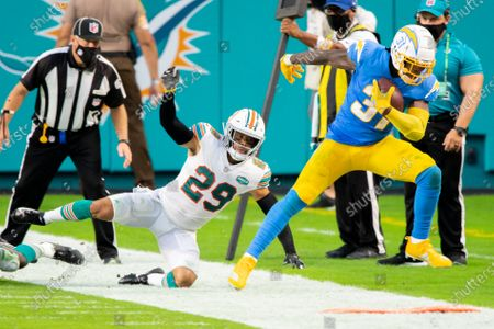 Los Angeles Chargers running back Kalen Ballage (31) runs with the ball and is pushed out of bounds by Miami Dolphins safety Brandon Jones (29) during an NFL football game, in Miami Gardens, Fla