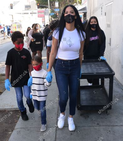 Stock Picture of Wolfe Lee Leissner, Gary Lee Leissner, Kimora Lee Simmons and Ming Lee Simmons hand out Thanksgiving meals to homeless residents of Skid Row's Housing Trust's Star Apartments