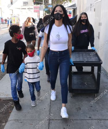 Stock Image of Wolfe Lee Leissner, Gary Lee Leissner, Kimora Lee Simmons and Ming Lee Simmons hand out Thanksgiving meals to homeless residents of Skid Row's Housing Trust's Star Apartments