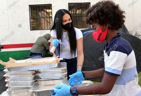Kimora Lee Simmons and Kenzo Lee Hounsou hand out Thanksgiving meals to homeless residents of Skid Row's Housing Trust's Star Apartments