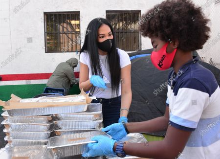 Stock Image of Kimora Lee Simmons and Kenzo Lee Hounsou hand out Thanksgiving meals to homeless residents of Skid Row's Housing Trust's Star Apartments
