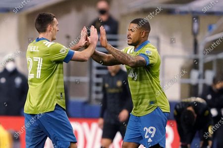 Seattle Sounders' Shane O'Neill (27) and Roman Torres (29) congratulate each other after the Sounders' 3-1 win over Los Angeles FC in an MLS playoff soccer match, in Seattle