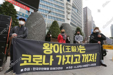 """Protesters stage a rally to oppose a planned visit by Chinese Foreign Minister Wang Yi near the Chinese Embassy in Seoul, South Korea, . Wang is set to arrive in Seoul on Wednesday for talks with Foreign Minister Kang Kyung-wha. The banner reads: """"Wang Yi goes out with the Corona"""