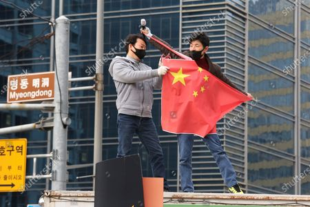 Protesters tear a Chinese national flag during a rally to oppose a planned visit by Chinese Foreign Minister Wang Yi near the Chinese Embassy in Seoul, South Korea, . Wang is set to arrive in Seoul on Wednesday for talks with Foreign Minister Kang Kyung-wha