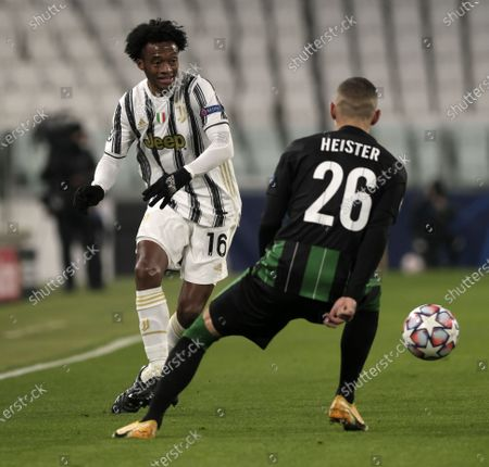 Stock Image of Juventus' Juan Cuadrado (L) vies with Ferencvaros' Marcel Heister during the UEFA Champions League group G match between Juventus and Ferencvaros in Turin, Italy, Nov. 24, 2020.