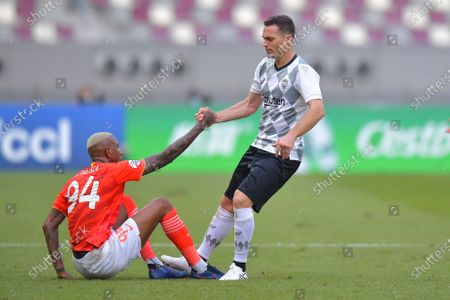 Anderson Talisca (L) of Evergrande gets help from Kobe player Thomas Vermaelen during the AFC Champions League group G match between Guangzhou Evergrande and Vissel Kobe at the Khalifa International Stadium in Doha, Qatar, 25 November 2020.