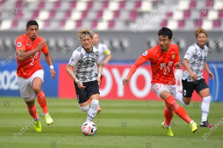 Stock Photo of Kyogo Furuhashi (2-L) of Kobe in action against Jiang Guangtai (L) and Park Ji-Soo of Evergrande during the AFC Champions League group G match between Guangzhou Evergrande and Vissel Kobe at the Khalifa International Stadium in Doha, Qatar, 25 November 2020.