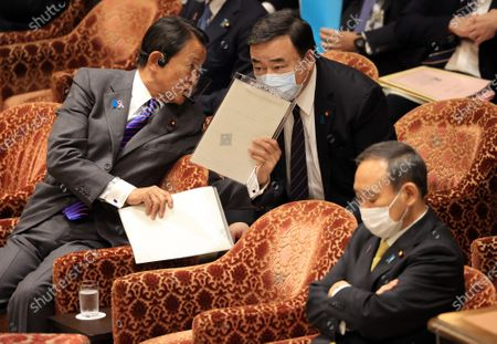 Japanese Finance Minister Taro Aso (L) discusses with Economy, Trade and Industry Minister Hiroshi Kajiyama (C) while Prime Minister Yoshihide Suga (R) waits to open Lower House's budget committee session at the National Diet in Tokyo on Wednesday, November 25, 2020.