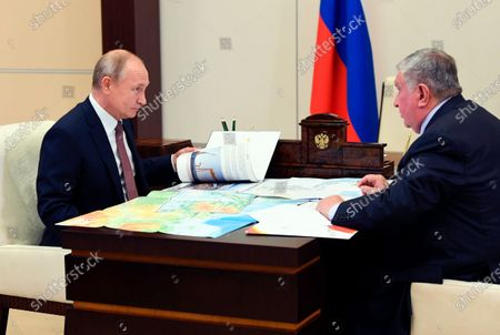 Stock Photo of Russian President Vladimir Putin, left, listens to Russian CEO of Rosneft oil company Igor Sechin during their meeting at the Novo-Ogaryovo residence outside Moscow, Russia