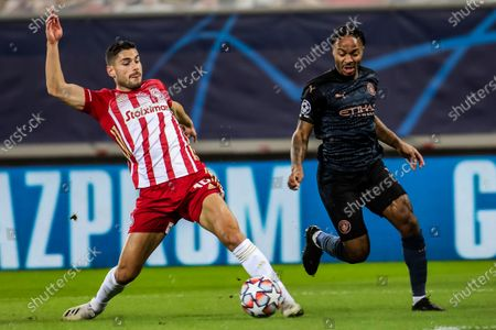 Olympiacos's Giorgos Masouras (L) vies for the ball with Manchester City's Raheem Sterling