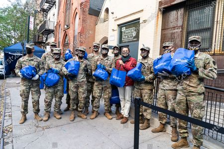 Assemblymember Robert Rodriguez (red jacket) helps to distribute turkey with members of National Guards and Governor Andrew Cuomo (not pictured) to needy families during pandemic at NY Common Pantry. Many people because of pandemic lost their jobs, income and slipped behind on rent, they started to rely on many pantries around the state to receive free groceries and produce. That is American tradition to have turkey for dinner on Thanksgiving Day holiday and Governor Cuomo helped organize distribution of Butterball and Shady Brook Farms turkeys. Governor as well as Common Pantry volunteers and staff and members of National Guards were wearing special facial mask â€oeDon't be a turkey, wear a maskâ€� to make a statement that COVID-19 is still a threat.