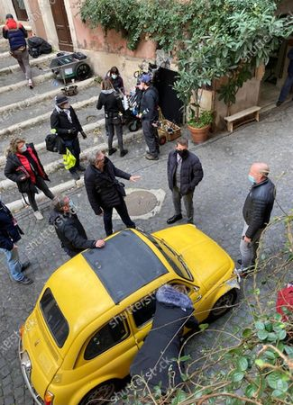 Tom Cruise (2-R) stands next to a yellow vintage car during the filming of the movie 'Mission: Impossible - Lybra' at the Monti district in Rome, Italy, 25 November 2020. The seventh installment in the Mission Impossible film series is to be released in 2021.