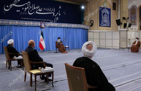 Iran's Supreme Leader Ayatollah Ali Khamenei shows Khamenei (C) speaking to president Hassan Rouhani (L) during a meeting with Iranian government over the economic crisis in Tehran, while mask-clad due to the Covid-19 coronavirus pandemic.