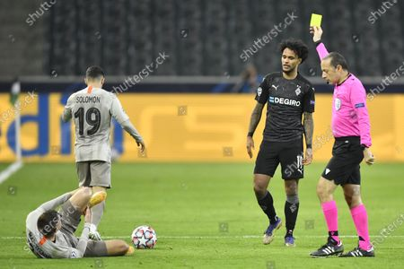 Referee Cuneyt Cakir, right, shows a yellow card to Moenchengladbach's Valentino Lazaro, second right, after he tacked Shakhtar's Mykola Matviyenko during the Champions League, Group B, soccer match between Borussia Moenchengladbach and Shakhtar Donetsk at the Borussia Park in Moenchengladbach, Germany