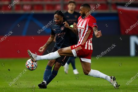 Manchester City's Raheem Sterling, left, fights for the ball with Olympiacos' Yann M'Vila During the Champions League, group C soccer match between Olympiacos and Manchester City at Georgios Karaiskakis stadium in Piraeus port, near Athens