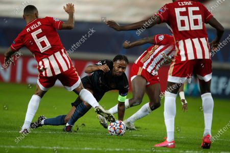 Stock Image of Manchester City's Raheem Sterling, centre, challenges for the ball with three Olympiakos players during the Champions League, group C soccer match between Olympiacos and Manchester City at Georgios Karaiskakis stadium in Piraeus port, near Athens