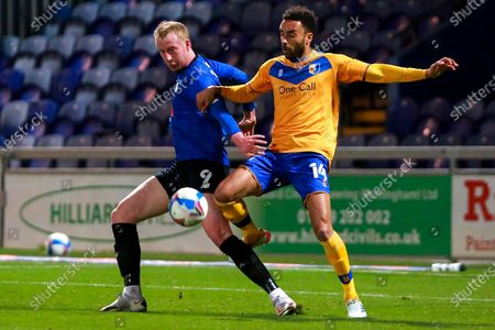 Mark Beck of Harrogate Town and James Perch of Mansfield Town tussle for the ball