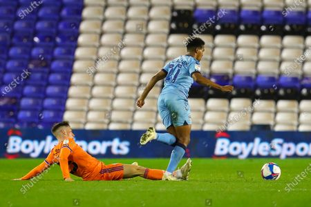 Harry Wilson of Cardiff City trips Sam McCallum of Coventry City (on loan from Norwich City), leading to a free kick
