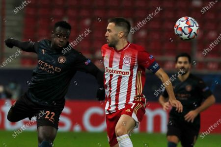 Manchester City's Benjamin Mendy, left, and Olympiacos' Kostas Fortounis, challenges for the ball during the Champions League, group C soccer match between Olympiacos and Manchester City at Georgios Karaiskakis stadium in Piraeus port, near Athens