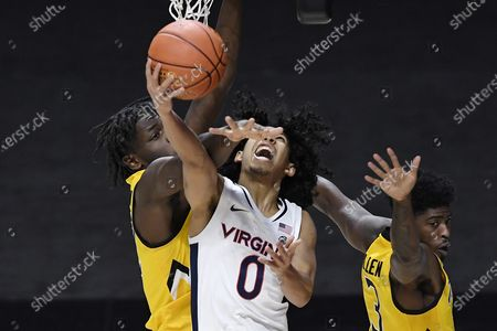 Virginia's Kihei Clark, center, is fouled by Towson's Charles Thompson, left, as Towson's Cam Allen, right, defends in the second half of an NCAA college basketball game, in Uncasville, Conn