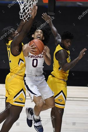 Virginia's Kihei Clark, center, shoots as Towson's Charles Thompson, left, and Towson's Cam Allen, right, defend in the second half of an NCAA college basketball game, in Uncasville, Conn