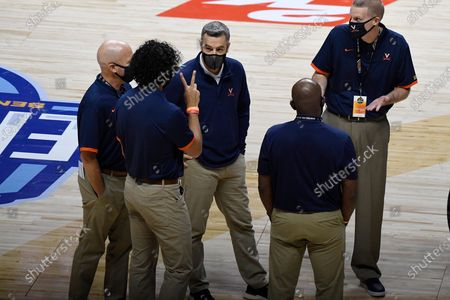 Virginia head coach Tony Bennett, center, meets with his coaching staff during a time out in the first half of an NCAA college basketball game against Towson, in Uncasville, Conn