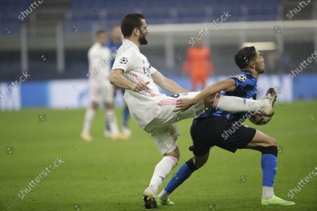 Inter Milan's Achraf Hakimi, right, and Real Madrid's Nacho vie for the ball during the Group B, Champions League soccer match between Inter Milan and Real Madrid at the San Siro Stadium, in Milan, Italy