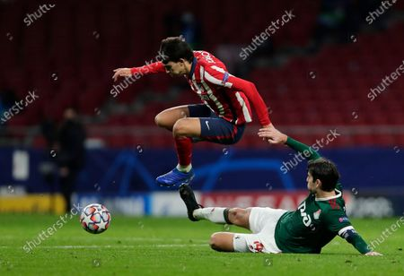 Lokomotiv's Vedran Corluka, right, tries to stop Atletico Madrid's Joao Felix during the Champions League group A soccer match between Atletico Madrid and Lokomotiv Moscow at the Wanda Metropolitano stadium in Madrid, Spain