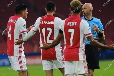 Ajax's Edson Alvarez, Noussair Mazraoui and David Neres argue with Referee Sergei Karasev of Russia over a penalty call during the group D Champions League soccer match between Ajax and Midtjylland at the Johan Cruyff ArenA in Amsterdam, Netherlands