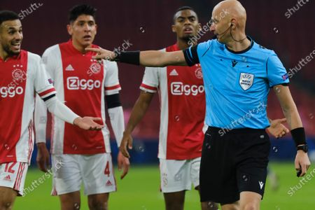 Ajax's Noussair Mazraoui, Edson Alvarez and Ryan Gravenberch, from left, argue with Referee Sergei Karasev of Russia over a penalty call during the group D Champions League soccer match between Ajax and Midtjylland at the Johan Cruyff ArenA in Amsterdam, Netherlands