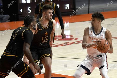 Stock Picture of Illinois' Jacob Grandson (3) looks to pass the ball as North Carolina A&T's Quentin Jones (4) and Harry Morrice (14) defend during the first half of an NCAA college basketball game, in Champaign, Ill