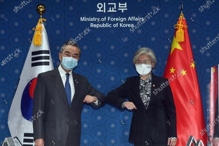 Chinese Foreign Minister Wang Yi (L) and his South Korean counterpart Kang Kyung-wha bump elbows before they begin talks in Seoul, South Korea, 26 November 2020.