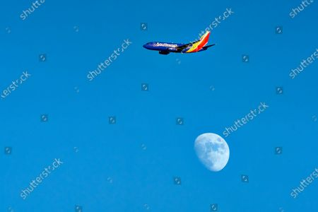 Stock Picture of A Southwest Airlines jet departing from John Wayne Airport flying above Huntington Beach, California.