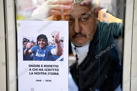 Stock Photo of Salvatore Daniele, brother of Neapolitan singer Pino Daniele stand with a photo Diego Maradona, on the windows of his house on the ground floor of an alley in the historic center of Naples, Italy, 26 November 2020. Soccer legend Diego Maradona died on 25 November at the age of 60 after a heart attack.