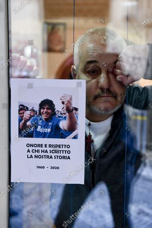 Salvatore Daniele, brother of Neapolitan singer Pino Daniele stand with a photo Diego Maradona, on the windows of his house on the ground floor of an alley in the historic center of Naples, Italy, 26 November 2020. Soccer legend Diego Maradona died on 25 November at the age of 60 after a heart attack.