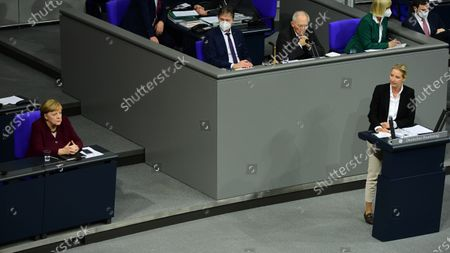 German Chancellor Angela Merkel (L) sits on her place after delivering a speech to the German Bundestag as Alternative for Germany party (AfD) faction co-chairwoman in the German parliament Bundestag and deputy chairwoman Alice Weidel (R) speaks in Berlin, Germany, 26 November 2020. Merkel delivered a government declaration to the members of the German parliament Bundestag on how to cope with the Covid-19 pandemic situation.