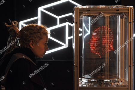 Stock Photo of A visitor views a shape of a 3-D shape of a male head created by LED's created by Vincent Leclerc of Revolver