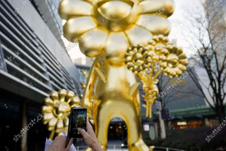 A passerby takes pictures of the artwork 'Flower Parent and Child' by Japanese contemporary artist Takashi Murakami displayed at Roppongi Hills 66 Plaza in Tokyo, Japan, 26 November 2020. Weighing over 11 tons, the 10 meters high golden 'Flower Parent and Child' sculpture is one of Murakami's largest artworks.